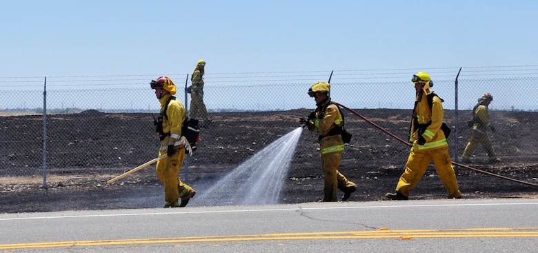 Beale firefighters extinguish the remnants of a fire that burned outside the Doolittle Gate at Beale Air Force Base, Calif., June 11, 2012. Beale firemen often support local fire departments during the fire season. (Courtesy photo by Noelle Hoffman)