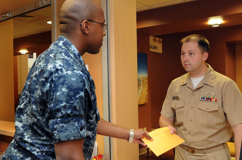 Petty Officer 2nd Class Japheth Tillman hands Chief Petty Officer Mark Harris a envelope containing images of Harris's x-ray images. Once X-rays, Magnetic Resonance Imaging or any other examination has been reviewed and findings are reported, the images are burned to a CD for a patient to pick up to get the images to the requesting doctor who may be located out in town. Tillman is a hospital corpsman assigned to Naval Health Clinic Charleston and Harris is a machinist's mate assigned to Navy Nuclear Power Training Unit as an instructor at Joint Base Charleston – Weapons Station. (U.S. Navy photo/Petty Officer 1st Class Jennifer Hudson)
