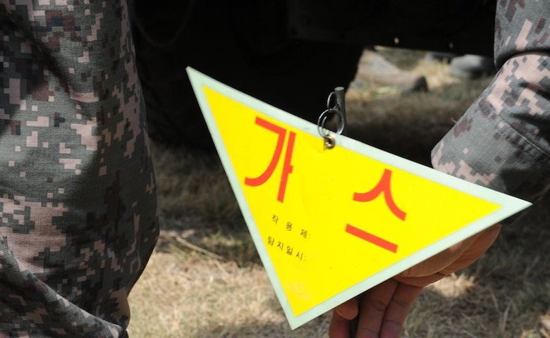 A warning sign is retrieved after being ejected from a decontamination vehicle used by Republic of Korea Air Force members during training with Pacific Air Forces bases June 8, 2012, at Kunsan Air Base, Republic of Korea. The capability to detect contaminants without leaving a vehicle is a unique one for the ROKAF. (U.S. Air Force photo/Senior Airman Brigitte N. Brantley)
