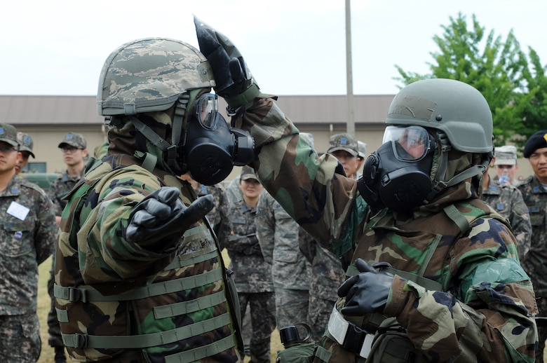 Staff Sgt. Ashley Bartlett, right, 8th Civil Engineer Squadron, decontaminates Master Sgt. Jeffrey Randall, 8th CES, during a demonstration of a contamination control area for Republic of Korea Air Force members June 8, 2012, at Kunsan Air Base, Republic of Korea. Because U.S. and South Korean forces would work together during a chemical, biological, radiological or nuclear attack, being familiar with the other's equipment and procedures is important. (U.S. Air Force photo/Senior Airman Brigitte N. Brantley)