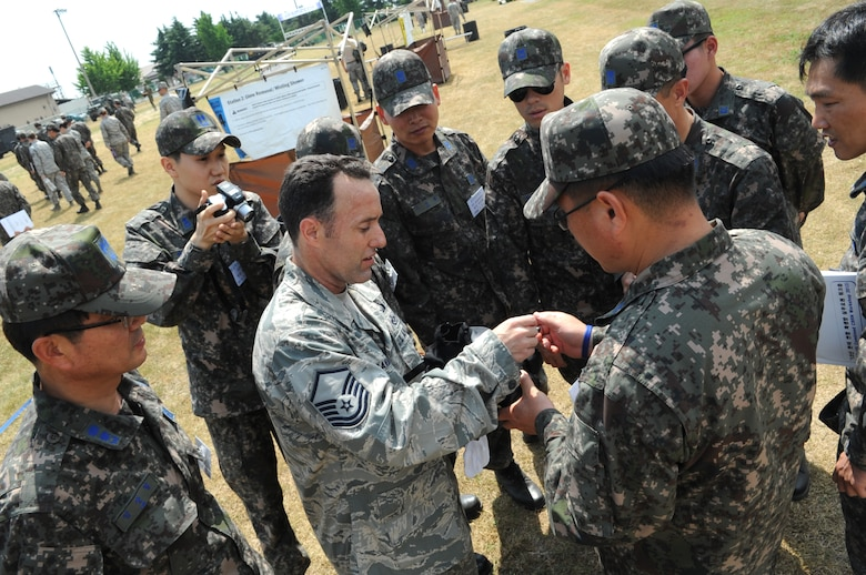 Master Sgt. Jeffrey Randall, 8th Civil Engineer Squadron emergency management flight superintendent, discusses the M-50 gas mask with Republic of Korea Air Force members from the 38th Fighter Group June 8, 2012, at Kunsan Air Base, Republic of Korea. Because U.S. and South Korean forces would work together during a chemical, biological, radiological or nuclear attack, being familiar with the other's equipment and procedures is helpful. (U.S. Air Force photo/Senior Airman Brigitte N. Brantley)