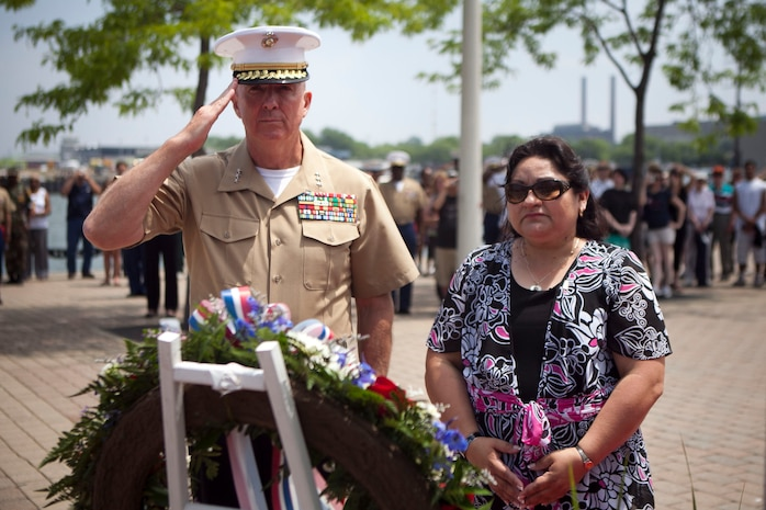 Lt. Gen. Steven A. Hummer, commander of Marine Forces Reserve and Marine Forces North, and Sandra Mandez-Ruiz, a Gold Star family member, listen to the playing of taps at a wreath laying ceremony at traveling Vietnam War Memorial Wall at Voinovich Park here June 12. Voinovich Park is one of the sites of displays available for public during the Marine Week Cleveland. Along with the wall, Marine Corps vehicles, aircraft and equipment will be available for viewing at Public Square, Voinovich Park, Gateway Plaza and Rock and Roll Hall of Fame. Marine Week Cleveland celebrates community, country and the Corps. More than 750 Marines journeyed to Cleveland for the event, which runs through June 17. Ohio has more than 9,000 active and reserve Marines, making it one of the top-five producers of Marines.