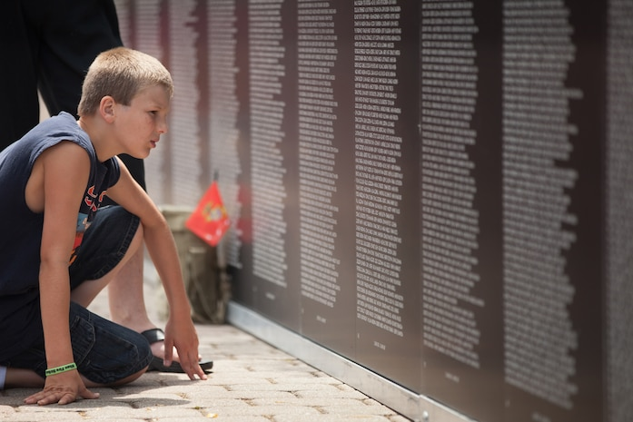 Hunter Mora, grandson of Marine Vietnam War veteran Donald Mora, looks for the names of his granddad's fallen comrades from the war at the traveling Vietnam War Memorial Wall in Voinovich Park in Cleveland June 12, 2012. Mora served from 1963-1969 and lost 12 of his close friends. Seeing the names of fallen comrades was difficult for Mora and brought back a lot of emotions, he said. A Marine sentry stands guard at the wall from 8 a.m.-10 p.m., and Marine veteran Cleveland police officers volunteered to take the night shifts. More than 750 Marines will be in Cleveland all week displaying Marine aircraft, vehicles and equipment, as well as interacting and sharing with the public the values and character of the Marine Corps. One of the culminating events will be a Marine Air Ground Task Force demonstration, which showcases Marines' ability to assault from ship-to-shore via ground and air, June 16-17 at Burke Lakefront Airport.
