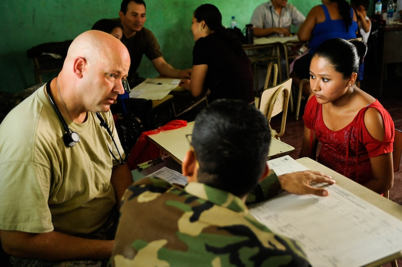 Air Force Capt. Jeff Herchler, Medical Element physician assistant, listens to an El Salvadoran military member for a translation of a patient's concerns. In partner with the country's Ministry of Health and military, JTF-Bravo recently provided care to 776 local patients in the municipalities of El Castano and Rancho San Marcos, El Salvador, during a two-day joint Medical Readiness Training Exercise. (U.S. Air Force photo/1st Lt. Christopher Diaz)