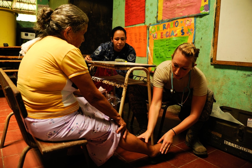 Air Force 1st Lt. Jess Looft, Joint Task Force-Bravo Medical Element nurse, checks a patient's leg for swelling during a two-day joint Medical Readiness Training Exercise in partner with El Salvador's Ministry of Health and military. The team provided care to 776 local patients in the municipalities of El Castano and Rancho San Marcos, El Salvador. (U.S. Air Force photo/1st Lt. Christopher Diaz)