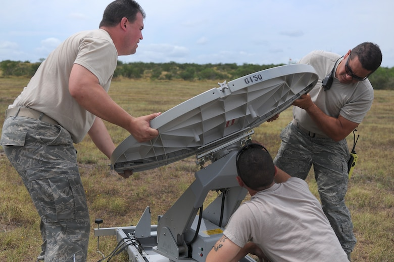 Master Sgt. David Nickell, a technician with Detachment 1, assists Staff Sgts. Joshua Cash (left) and Joseph Dawson (right), members of the 149th Communications Flight, both subcomponents of the Texas Air National Guard's 149th Fighter Wing, install a TRACSTAR satellite uplink device, which provided mobile communications for the Texas Red Flag exercise at Yankee Range, in McMullen County, on June 1, 2012. (Air National Guard photo by Senior Master Sgt. Mike Arellano / Released)