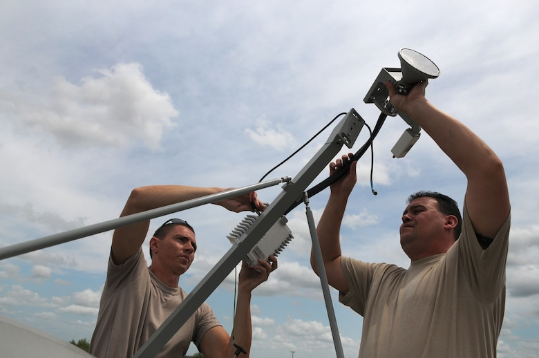 Staff Sgts. Joshua Cash (left) and Joseph Dawson (right), members of the 149th Communications Flight, a subcomponent of the Texas Air National Guard's 149th Fighter Wing, install a TRACSTAR satellite uplink device, which provided mobile communications for the Texas Red Flag exercise at Yankee Range, in McMullen County, on June 1, 2012. (Air National Guard photo by Senior Master Sgt. Mike Arellano / Released)