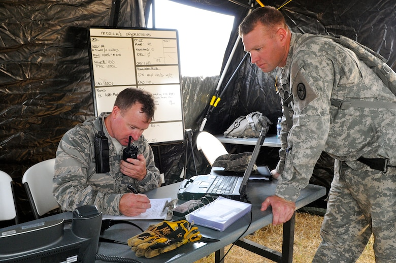 Air Force Capt. Wayne Hill (left), a medical plans and operations officer, coordinates activities as the officer-in-charge of the air medical operations with Army Staff Sgt. Kevin Creasy, noncommissioned officer-in-charge of 6 CERF-P tactical operations center, during an emergency preparedness exercise in Austin, Texas, on Apr. 26, 2012. (Air National Guard photo by Senior Master Sgt. Mike Arellano / Released)