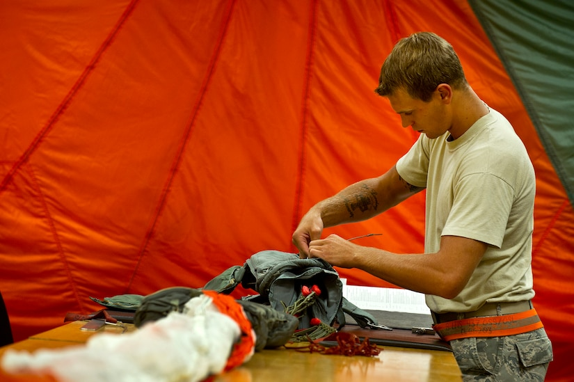 Senior Airman Benjamin Leis, an aircrew flight equipment technician with the 437th Operations Support Squadron out of Joint Base Charleston - Air Base, S.C., prepares a parachute to be packed for a C-17A Globemaster III, June 8, 2012. The Airmen swap out and inspect equipment for C-17A alert aircraft on standby every 30 days. (U.S. Air Force photo by Airman 1st Class George Goslin/Released)