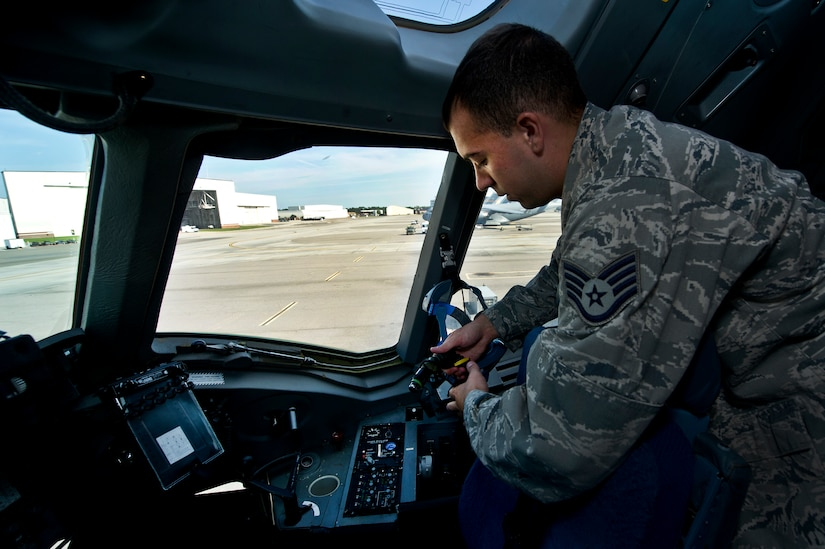 Staff Sgt. Kyle Pratt, an aircrew flight equipment technician with the 437th Operations Support Squadron out of Joint Base Charleston - Air Base, S.C., swaps out Quick Don oxygen masks on a C-17A Globemaster III, June 8, 2012. The Airmen swap out and inspect equipment for C-17A alert aircraft on standby every 30 days. (U.S. Air Force photo by Airman 1st Class George Goslin/Released)