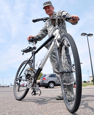 Lt. Col. Clinton Burpo stands with his trusty bicycle at McConnell Air Force Base, Kan., June 12, 2012. Burpo has logged more than 21,700 miles on his bicycle since he began using it to commute to and from work in 2006. Burpo is a 931st Air Refueling Group logistics readiness officer, (U.S. Air Force photo/1st Lt. Zach Anderson)