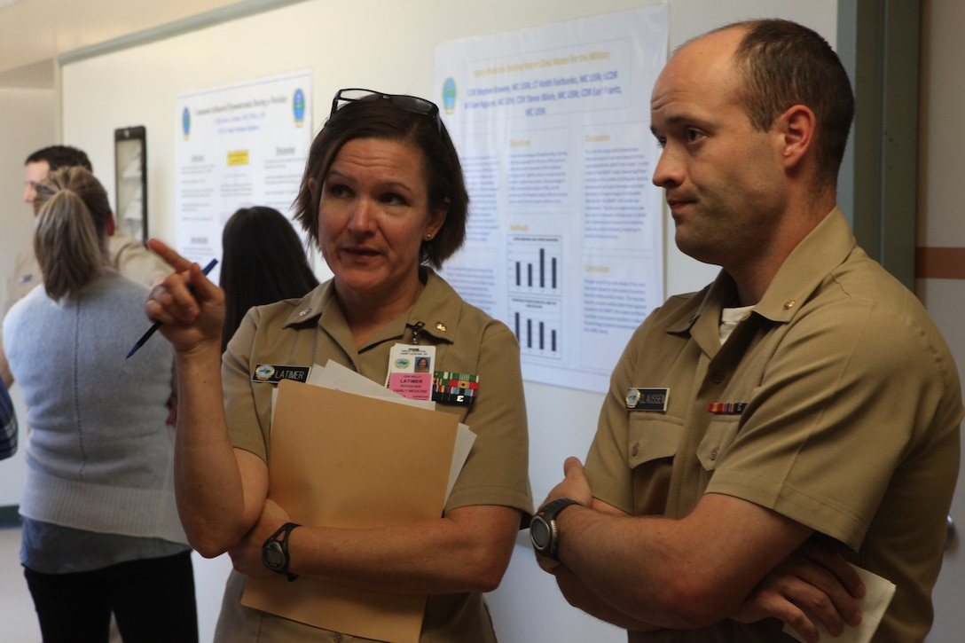 Cmdr. Kelly Latimer, assistant director of residency, give feedback to a resident on his research project during Naval Hospital Camp Lejeune's second annual Research Symposium aboard Marine Corps Base Camp Lejeune June 8. Residents presented a variety of different ideas and hypotheses at the symposium to be judged.
