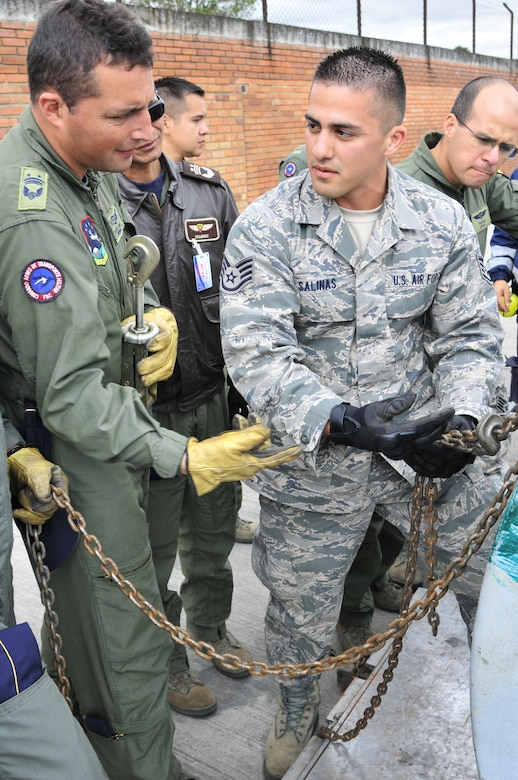 Staff Sgt. Peter Salinas, 571st Mobility Support Advisory Squadron air transportation air advisor, explains to Técnico Subjefe Hector Sierra, Colombian air force, how to properly connect chains to build a chain bridle during the final day of the equipment preparation seminar June 8 at Commando Aéreo de Transporte Militar, Bogota, Colombia.  Chains are used on heavy single items, whereas nets are used for bulk cargo.  (U.S. Air Force photo by Tech. Sgt. Lesley Waters)