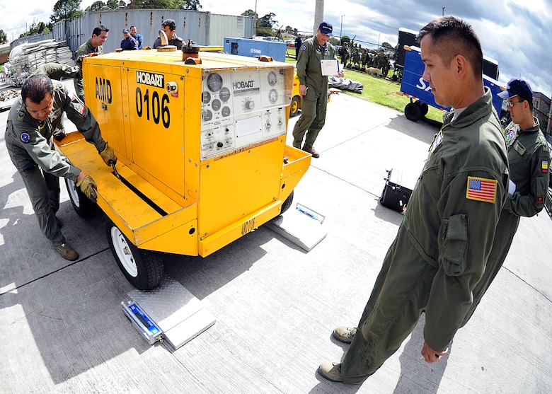 Staff Sgt. Jorge Borges, 571st Mobility Support Advisory Squadron loadmaster, looks on as members of the Colombian air force roll a generator on to two portable scales to calculate the center of balance of the generator during the hands on pallet build-up seminar June 6 at Commando Aéreo de Transporte Militar, Bogota, Colombia.  (U.S. Air Force photo by Tech. Sgt. Lesley Waters)