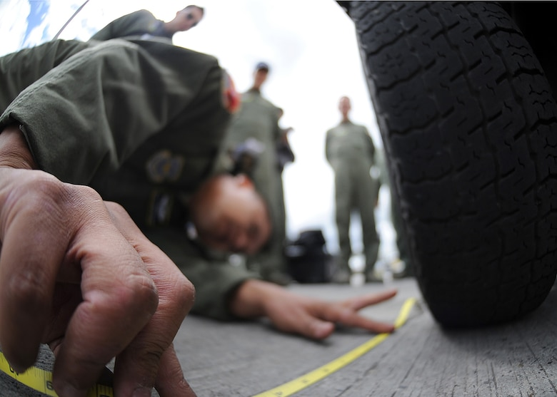 Staff Sgt. Jorge Borges, 571st Mobility Support Advisory Squadron loadmaster, measures the foot print of the front tire during the cargo build up seminar June 6 at Commando Aéreo de Transporte Militar, Bogota, Colombia.  The foot print is to calculate the PSI of the generator.  (U.S. Air Force photo by Tech. Sgt. Lesley Waters)