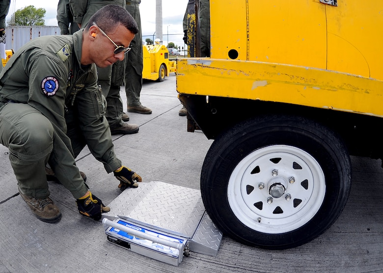 Técnico Primero Jorge Barragan, Colombian air force member, positions the portable scale before weighing the rolling stock during the pallet build-up seminar June 6 at Commando Aéreo de Transporte Militar, Bogota, Colombia.  (U.S. Air Force photo by Tech. Sgt. Lesley Waters)