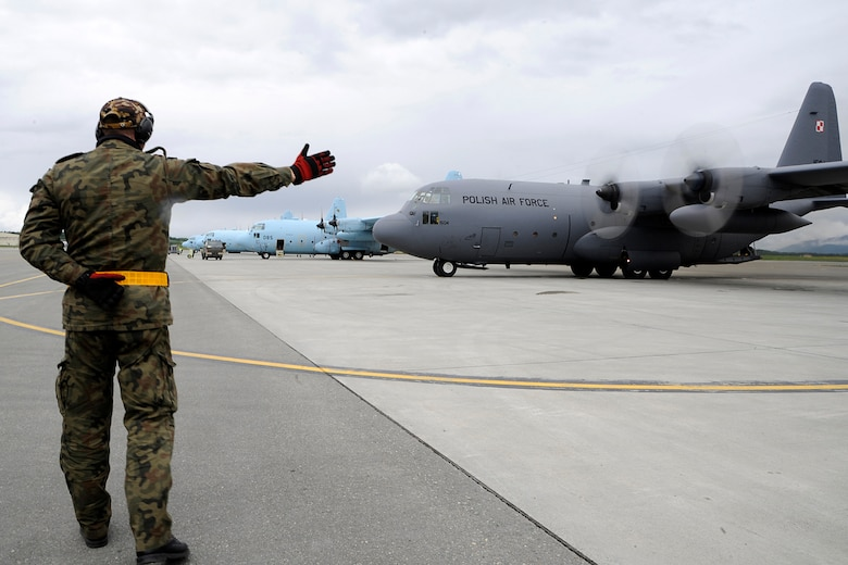 A member of the Polish Air Force C-130 Hercules crew guides the aircraft to begin to taxi to the runway during Red Flag-Alaska on Joint Base Elmendorf-Richardson June 13, 2012. The goal of Red Flag-Alaska is to provide each aircrew with vital first missions to increase their chances of survival in combat environments. (U.S. Air Force photo/Staff Sgt. Zachary Wolf)