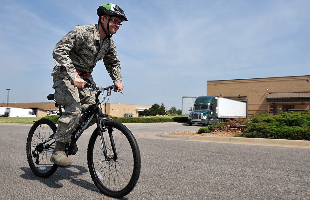 Airman 1st Class Ian Shearman,  22nd Maintenance Squadron aircraft structural maintenance apprentice, rides his bicycle June 14, 2012, McConnell Air Force Base, Kan.  Taking safety measures in traffic and wearing proper equipment shields against potential injuries while bicycling. (U.S. Air Force illustration/Airman 1st Class Maurice A. Hodges)