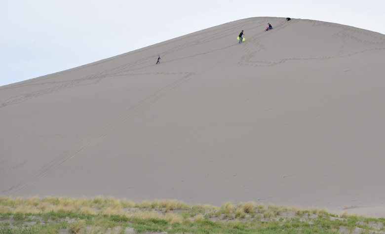 A family climbs a sand dune at Bruneau Dunes State Park, Idaho, June 7, 2012. The state park includes desert, dune, prairie, lake and marsh habitat. Some popular activities include fishing, bird watching, camping, hiking, swimming and viewing the stars at one of only two public observatories in Idaho. (U.S. Air Force photo/Airman 1st Class Heather Hayward)