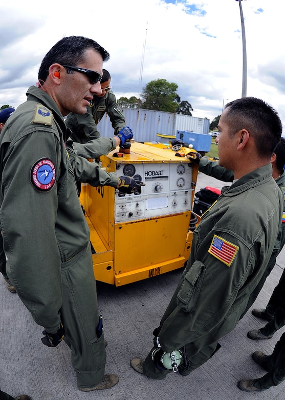 Técnico Primero Cifilfredo Rojas, Colombian air force, and Staff Sgt. Javier Borges, 571st Mobility Support Advisory Squadron loadmaster air advisor, verifies the fuel quantity of the Hobart generator for loading onto aircraft during the hands on pallet build-up seminar June 6 at Commando Aéreo de Transporte Militar, Bogota, Colombia.  (U.S. Air Force photo by Tech. Sgt. Lesley Waters)
