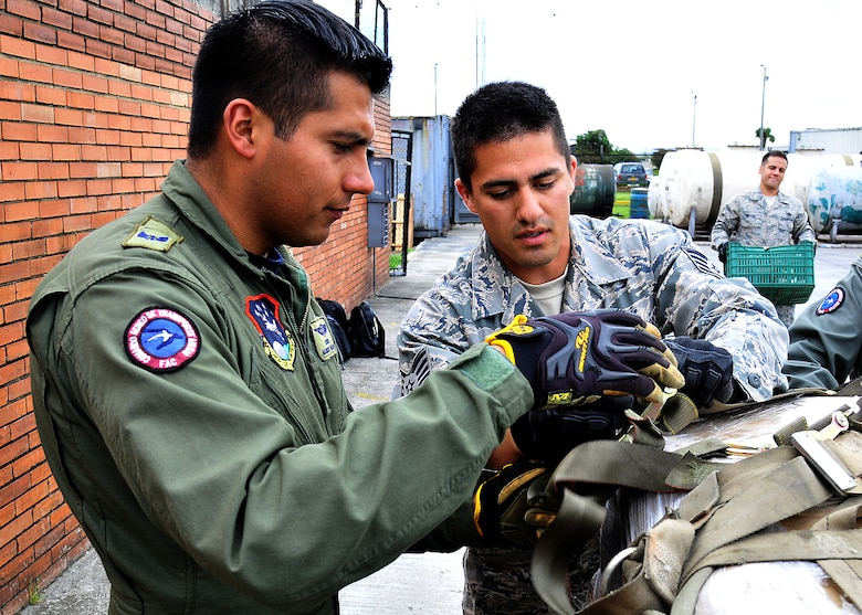 Staff Sgt. Peter Salinas, 571st Mobility Support Advisory Squadron air transportation air advisor, works with Técnico Edwin Camacho, Colombian air force, secure cargo straps during the hands on pallet build-up seminar June 6 at Commando Aéreo de Transporte Militar, Bogota, Colombia.  (U.S. Air Force photo by Tech. Sgt. Lesley Waters)