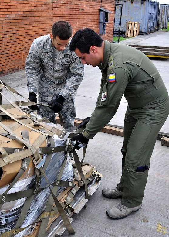 Staff Sgt. Angel Ortega, 571st Mobility Support Advisory Squadron air transportation air advisor, works with Técnico Cuarto Cesar Gomez, Colombian air force, on properly securing cargo during the pallet build-up seminar June 6 at Commando Aéreo de Transporte Militar, Bogota, Colombia.  (U.S. Air Force photo by Tech. Sgt. Lesley Waters)