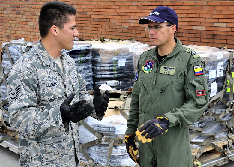 Staff Sgt. Peter Salinas, 571st Mobility Support Advisory Squadron aerial transportation air advisor, explains the limitations for using the top net with Técnico Subjefe Jhon Ayala, Colombian air force, during the hands on pallet build-up seminar June 6 at Commando Aéreo de Transporte Militar, Bogota, Colombia.  The Colombian air force is participating for the first time in this year's Red Flag exercise at Nellis AFB, Nev., July 16-27.  (U.S. Air Force photo by Tech. Sgt. Lesley Waters)