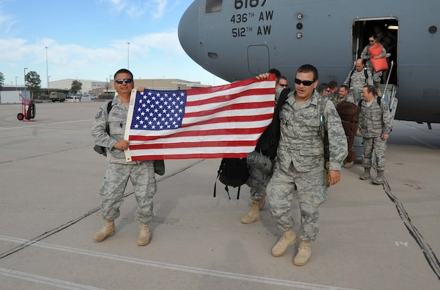 Master Sgt. Augstin Luera with the 943rd Maintenance Squadron and Tech. Sgt. Thomas Hernandez with the 305th Rescue Squadron hold up an American flag as they both depart a C-17 Globemaster III on the flight line at Davis Monthan Air Force Base, Ariz. More than 70 Reserve Airmen from the 943rd Rescue Group here returned home June 9 through the 19th after a four month deployment at Camp Bastion, Afghanistan providing medical evacuation capabilities in Afghanistan's Regional Command Southwest. (U.S. Air Force Photo/ Master Sgt. Luke Johnson)