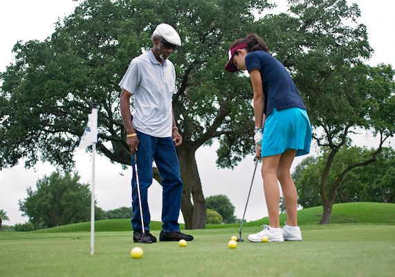 Bill Boykin, a volunteer coach, instructs Hannah Henderson on proper putting techniques June 13 at the annual Junior Golf Clinic at Joint Base San Antonio-Randolph Oaks Golf Course, JBSA-Randolph, Texas. (U.S. Air Force photo by Benjamin Faske)