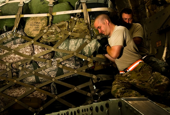 Senior Airman Robert Taylor (front), 455th Expeditionary Aerial Port Squadron Passenger Services representative and Tech. Sgt Nicholas Hotham (back), 455th Expeditionary Passenger Services Line supervisor, maneuver a cargo pallet aboard U.S. Air C-17 Globemaster III at Bagram Airfield, Afghanistan, June 7, 2012. Airmen with 455 EAPS serve up to 2,500 passengers daily. (U.S. Air Force photo/Capt. Raymond Geoffroy)