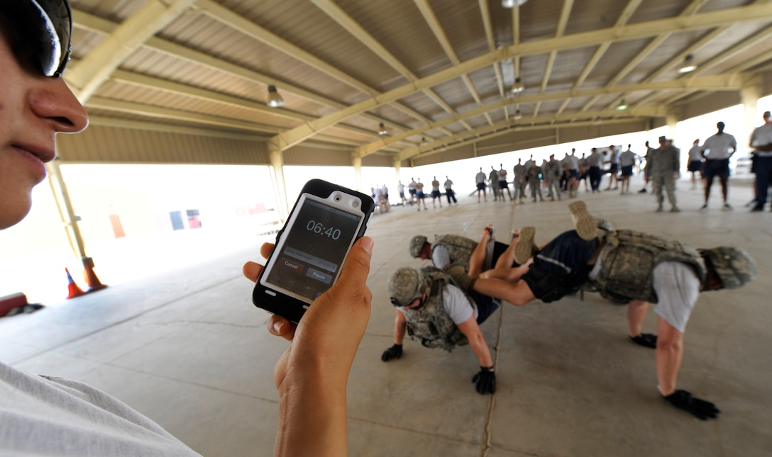 SOUTHWEST ASIA – A volunteer cadre from the 386th Expeditionary Security Forces Squadron times a 386th ESFS fire team at the first Defender Challenge here June 9, 2012. Each team had 10 minutes to do as many four-person buddy push-ups as they could. This team pushed out 65. (U.S. Air Force photo/Staff Sgt. Alexandra M. Boutte)