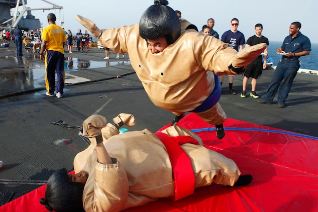Lance Cpl. Joshua Phillips, top, and Cpl. Zamar Aguon, Marine Fighter Attack Squadron 251 ordnance technicians, participate in a sumo-suit bout during a steel beach picnic aboard aircraft carrier USS Enterprise, June 15. The carrier is currently deployed to support maritime operations in the U.S. 5th Fleet area of responsibility.