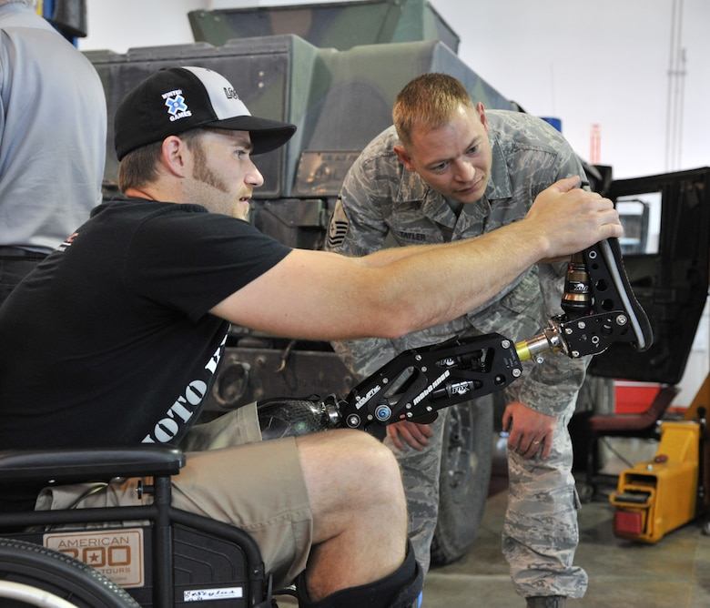 Mike Schultz explains the mechanics of his prosthetic leg and moto knee to Master Sgt. Justin Tayler, 341st Logistics Readiness Squadron vehicle fleet manager, when he was visiting them June 12 as part of the American300 Baja 1000 Tour. Schultz designed the prosthetic so he could continue to compete in both MotoX dirtbike and SnoX snowmobiling races. You can find out more about him at www.monstermikeschultz.com. (U.S. Air Force photo/John Turner)
