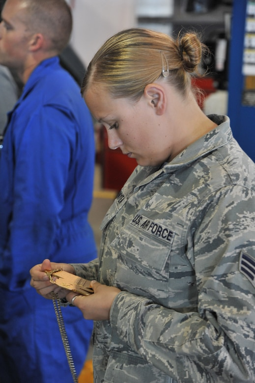 Senior Airman Danielle Bunyea, 341st Logistics Readiness Squadron vehicle management and analysis apprentice, looks at the gold medal Chris Ridgeway won at the Xgames in Los Angeles in the supercross adaptive competition. (U.S. Air Force photo/John Turner)