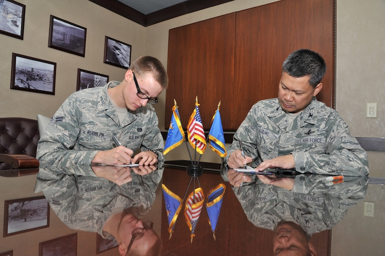 Airman 1st Class Rene Rudolph, 819th RED HORSE Squadron member, and Col. H.B. Brual, 341st Missile Wing commander, prepare to sign membership applications to join the Air Force Sergeants' Association on June 7.  The AFSA's next meeting is scheduled for June 29 at 11 a.m. at the Grizzly Bend.  (U.S. Air Force photo/ John Turner)