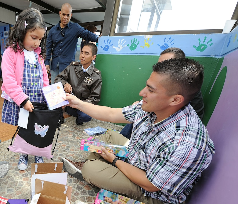 Staff Sgt. Peter Salinas, 571st Mobility Support Advisory Squadron air advisor, hands out donated items to children from the Asociación Amigos del Niño Ayudame, Bogota, Colombia June 9 as part of an Air Mobility Command Building Partner Capacity month-long mission.  Members of the Colombian air force, Inter-American Air Forces Academy and 12th Air Force (Air Forces Southern) also participated in the visit.  (U.S. Air Force photo by Tech. Sgt. Lesley Waters)