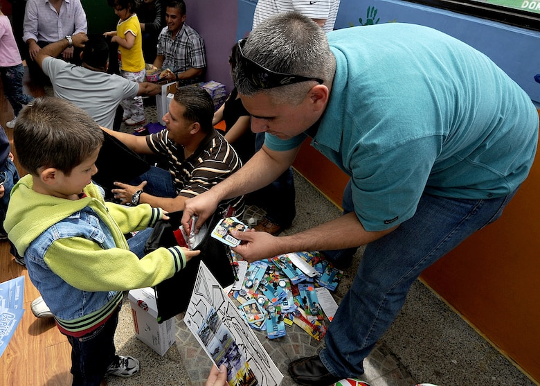 Master Sgt. Aaron Carrillo, 571st Mobility Support Advisory Squadron team sergeant, hands out donated items to children from the Asociación Amigos del Niño Ayudame, Bogota, Colombia June 9 as part of an Air Mobility Command Building Partner Capacity month-long mission.  Members of the Colombian air force, Inter-American Air Forces Academy and 12th Air Force (Air Forces Southern) also participated in the visit.  (U.S. Air Force photo by Tech. Sgt. Lesley Waters)