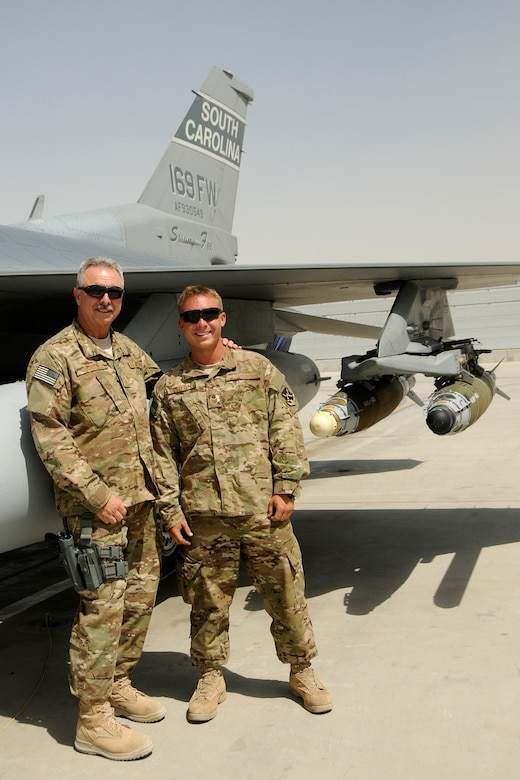 Chief Master Sgt. Dennis Burton, maintenance superintendent and his son, Tech. Sgt. Brandon Burton, a crew chief assigned to the 451st Expeditionary Aircraft Maintenance Squadron at Kandahar Airfield, Afghanistan, pose for a photo on the flight line by an F-16 Fighting Falcon June 13, 2012. Personnel are deployed from McEntire Joint National Guard Base, S.C., in support of Operation Enduring Freedom. Swamp Fox F-16's, pilots, and support personnel began their Air Expeditionary Force deployment early April to take over flying missions for the air tasking order and provide close air support for troops on the ground in Afghanistan.      (U.S. Air Force photo/TSgt. Caycee Cook)