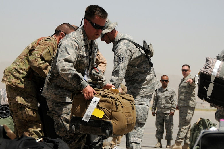 Captain Grady Patterson, the maintenance officer in charge assigned to the 451st Expeditionary Aircraft Maintenance Squadron at Kandahar Airfield, Afghanistan, helps unload luggage for members just arriving June 10, 2012. Members of the 169th Fighter Wing at McEntire Joint National Guard Base, S.C., are deployed in support of Operation Enduring Freedom. Swamp Fox F-16's, pilots, and support personnel began their Air Expeditionary Force deployment early April to take over flying missions for the air tasking order and provide close air support for troops on the ground in Afghanistan. (U.S. Air Force photo/TSgt. Caycee Cook)