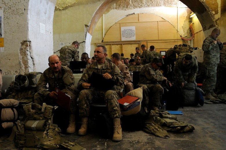 Senior Master Sgt. Tommy Claytor and Chief Master Sgt. Dennis Burton, from the 169th Maintenance Squadron at McEntire Joint National Guard Base, S.C., wait to begin in-processing after arriving at Kandahar Airfield, Afghanistan June 10, 2012. Members of the 169th Fighter Wing are deployed in support of Operation Enduring Freedom. Swamp Fox F-16's, pilots, and support personnel began their Air Expeditionary Force deployment early April to take over flying missions for the air tasking order and provide close air support for troops on the ground in Afghanistan. (U.S. Air Force photo/TSgt. Caycee Cook)