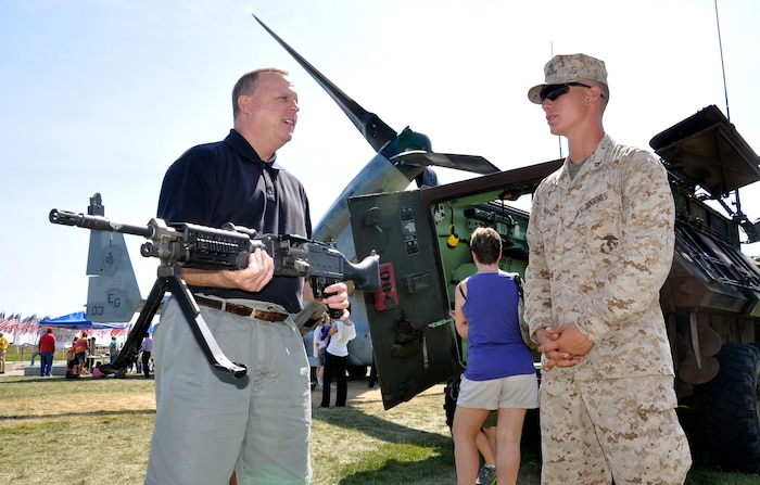 Rich Croll, a Toledo, Ohio, native, talks to Lance Cpl. Lee Brophy, with 2nd Light Armored Reconnaissance Battalion, based at Marine Corps Base Camp Lejeune, N.C., while holding a M230B machine gun at Voinovich Park in Cleveland June 15 during Marine Week Cleveland which ends June 17. Various  displays showcasing Marine Corps equipment, aircraft and technology are available for viewing at Gateway Plaza and Voinovich Park. More than 750 Marines are participating in Marine Week to commemorate the city's support for the military and celebrate community, country and Corps.
