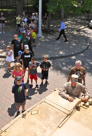 Children wait in line to explore the M1-A1 Abrams tank in Voinovich Park in Cleveland June 15 during Marine Week Cleveland which ends June 17. Various displays showcasing Marine Corps equipment, aircraft and technology are available for viewing at Gateway Plaza and Voinovich Park. More than 750 Marines are participating in Marine Week to commemorate the city's support for the military and celebrate community, country and Corps.