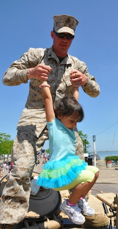 Sgt. Justin Taulbee, gunner of a M1-A1 Abrams tank, stationed at Fort Knox, Ky., assists Stella Rasch, 4, out of the tank in Voinovich Park in Cleveland June 15 during Marine Week Cleveland which ends June 17. Various  displays showcasing Marine Corps equipment, aircraft and technology are available for viewing at Gateway Plaza and Voinovich Park. More than 750 Marines are participating in Marine Week to commemorate the city's support for the military and celebrate community, country and Corps.