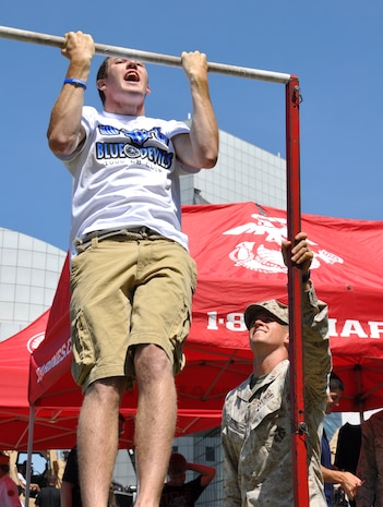 Capt. Travis Tufle, with 4th Marine Corps Recruiting District, observes as Jake Lonas, 17, does pull-ups at a recruiting post in Voinovich Park in Cleveland June 15 during Marine Week Cleveland which ends June 17. Various  displays showcasing Marine Corps equipment, aircraft and technology are available for viewing at Gateway Plaza and Voinovich Park. More than 750 Marines are participating in Marine Week to commemorate the city's support for the military and celebrate community, country and Corps.
