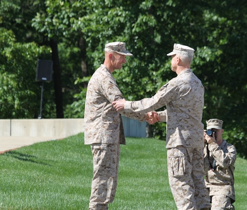 Col. John L. Mayer receives a congratulatory handshake from the Commandant of the Marine Corps Gen. James F. Amos during a change of command ceremony for the Wounded Warrior Regiment at the National Museum of the Marine Corps here.