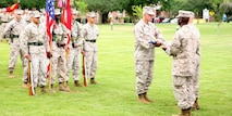 """Lt. Gen. Dennis J. Hejlik, commander, U.S. Marine Corps Forces Command, presents """"Old Glory"""" to Sgt. Maj. Greg W. Grizzle, the former senior enlisted advisor for the command who retired from the Marine Corps after the unit's relief and appointment ceremony, June 14. Grizzle who is a native of Iola, Kan., retired from the Marine Corps after more than 31 years of military service."""