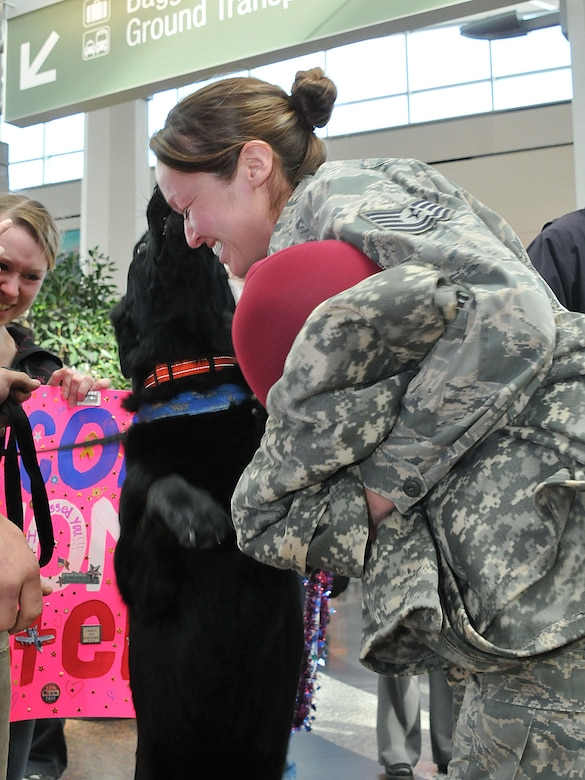ANCHORAGE, Alaska -- Tech. Sgt.Abigail Olivares, a utilities technician from the 176 Civil Engineer Squadron, is greeted by her pet dog at Ted Stevens International Airport here as she returns from deployment with a few of her commrades. Olivares was assigned to the 386 Expeditionary Civil Engineer Squadron for a six-month tour in Southwest Asia. National Guard Photo by Staff Sgt. N. Alicia Goldberger.