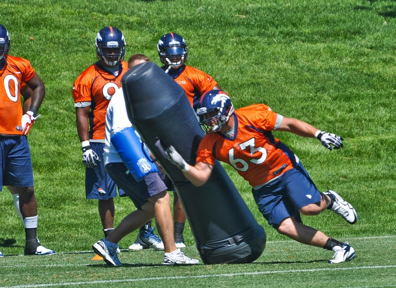 """ENGLEWOOD, Colo. – Benjamin Garland makes his way around a """"dummy bag"""" during a Denver Broncos mini-camp session June 13, 2012. Garland participated in the three-day mini-camp which took place from June 12-14. He is currently assigned to the 140 Wing Public Affairs Office, Colorado Air National Guard. (U.S. Air Force photo by Senior Airman Christopher Gross)"""