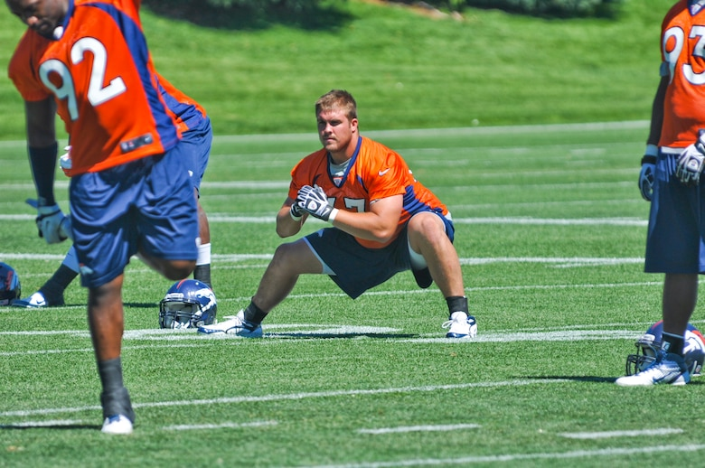 ENGLEWOOD, Colo. – Benjamin Garland stretches during a Denver Broncos mini-camp session June 13, 2012. Garland graduated with the Air Force Academy Class of 2010 and began his Air Force career as a strength and conditioning coach for the academy. He is currently assigned to the 140 Wing Public Affairs Office, Colorado Air National Guard. (U.S. Air Force photo by Senior Airman Christopher Gross)