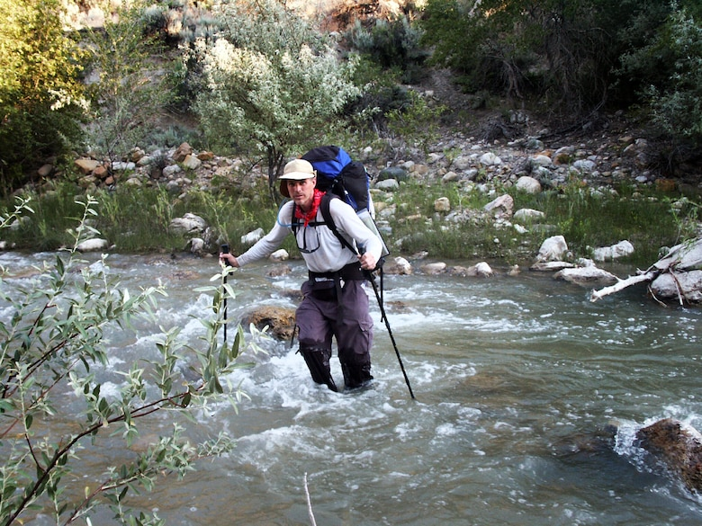 Jon Warnick crosses a river near Salina, Utah, during a walk across the state, summer of 2003.  The hike was part of a trek spanning from the bottom to the top of Utah to each boarder – a journey that took 43 days and was nearly 700 miles long.  (Courtesy photo)